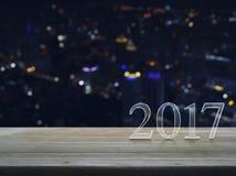 Texto de la Feliz Año Nuevo 2017 en la tabla de madera sobre ciudad de la noche de la falta de definición Imagen de archivo