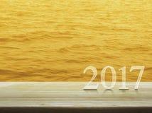 Texto de la Feliz Año Nuevo 2017 en la tabla de madera sobre el mar del agua del oro Imagen de archivo