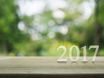 Texto de la Feliz Año Nuevo 2017 en la tabla de madera sobre vagos del árbol del verde de la falta de definición Imágenes de archivo libres de regalías