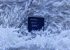 Texto de la Feliz Año Nuevo en tarjeta negra con las gotas de plata en la gripe blanca Fotos de archivo libres de regalías