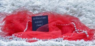 Texto de la Feliz Año Nuevo escrito en alemán en tarjeta negra con el tul rojo Imagen de archivo