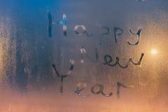 Texto de la Feliz Año Nuevo escrito en el vidrio tórrido Imagen de archivo libre de regalías