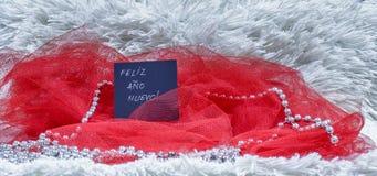 Texto de la Feliz Año Nuevo escrito en español en tarjeta negra con el tu rojo Foto de archivo
