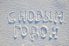 Texto de la Feliz Año Nuevo escrito en la lengua rusa en la nieve para la textura o el fondo - concepto de las vacaciones de invi Fotografía de archivo