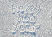Texto de la Feliz Año Nuevo escrito en la nieve para la textura o el fondo - concepto de las vacaciones de invierno Día soleado,  Fotografía de archivo