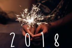 Texto 2018 de la Feliz Año Nuevo mano que lleva a cabo un firew ardiente de la bengala Fotografía de archivo