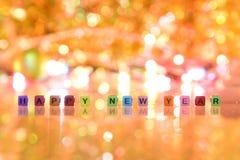 Texto de la Feliz Año Nuevo y fondo ligero caliente Fotografía de archivo