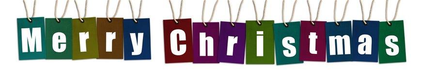 Texto de la Feliz Navidad en las etiquetas del multicolor aisladas en Backg blanco imagen de archivo