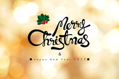 Texto de la Feliz Navidad y de la Feliz Año Nuevo 2017 en backg del bokeh del oro Foto de archivo libre de regalías