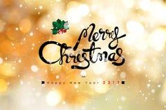 Texto de la Feliz Navidad y de la Feliz Año Nuevo 2017 en bokeh brillante del oro Imagen de archivo libre de regalías