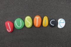 Texto de la justicia compuesto con las piedras coloreadas multi del mar sobre la arena volcánica negra stock de ilustración