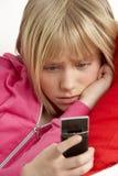 Texto de la lectura de la chica joven y el parecer preocupado Fotografía de archivo libre de regalías