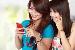 Texto de la mujer de dos asiáticos en su teléfono móvil Fotografía de archivo