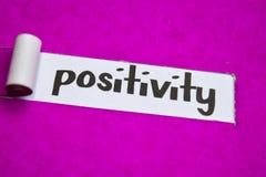 Texto de la positividad, concepto de la inspiración, de la motivación y del negocio en el papel rasgado púrpura imagen de archivo