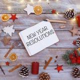 Texto de la resolución del Año Nuevo en cuaderno de notas en endecha del plano de la Navidad Foto de archivo libre de regalías