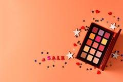 Texto de la venta en un fondo anaranjado Los productos de maquillaje de moda profesionales con los productos de belleza cosmético fotos de archivo