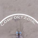 Texto de la zona de comodidad en la tierra, los pies y los zapatos del asfalto en piso Imágenes de archivo libres de regalías