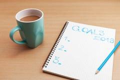 Texto de las metas 2018 en la nota de papel con la taza de café en la tabla del negocio, Fotos de archivo