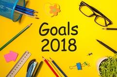 Texto de las metas 2018 en tablero amarillo con los materiales de oficina Las promesas del ` s del Año Nuevo para el próximo año, Fotografía de archivo