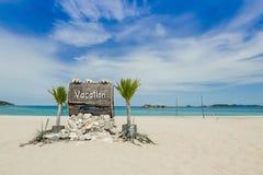 Texto de las vacaciones en muestra de madera en la playa Imágenes de archivo libres de regalías