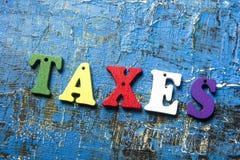 Texto de los impuestos en letras de madera coloridas ABC de madera en el fondo azul del grunge Fotos de archivo libres de regalías