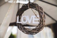 Texto de madeira do amor na grinalda trançada Fotografia de Stock