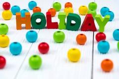 Texto de madera colorido del día de fiesta en el escritorio de madera blanco con la Navidad Foto de archivo