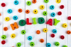 Texto de madera colorido del día de fiesta en el escritorio de madera blanco con la Navidad Imagen de archivo libre de regalías