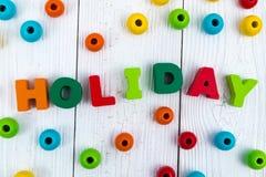 Texto de madera colorido del día de fiesta en el escritorio de madera blanco con la Navidad Imagen de archivo