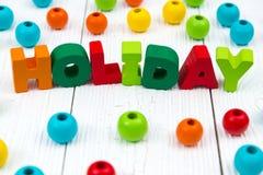Texto de madera colorido del día de fiesta en el escritorio de madera blanco con la Navidad Foto de archivo libre de regalías