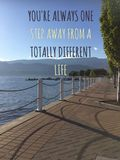 Texto de motivación inspirado en la opinión escénica del lago con la calzada del ladrillo a lo largo de la orilla del lago foto de archivo