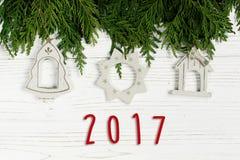 texto de 2017 muestras en los juguetes simples de la Navidad en las ramas de árbol verdes o Imagen de archivo