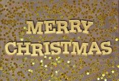 Texto de oro de la Feliz Navidad y estrellas de oro imagen de archivo