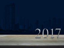 Texto de prata do metal do ano novo feliz 2017 na tabela de madeira sobre a cidade ilustração do vetor