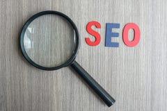 Texto de SEO Search Engine Optimization na nota amarela com papel e a lupa desintegrados no fundo de madeira da tabela ideia, foto de stock royalty free