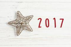 texto de 2017 sinais na estrela dourada do Natal em rústico branco à moda Fotografia de Stock Royalty Free