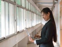 Texto de sorriso e de datilografia da mulher de negócio asiática foto de stock royalty free