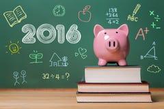 Texto del año 2016 con la hucha rosada encima de los libros Imágenes de archivo libres de regalías