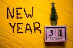 Texto del Año Nuevo del café en fondo de madera amarillo del tablón Fondo del Año Nuevo Imagen de archivo libre de regalías