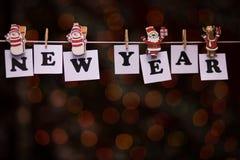 Texto del Año Nuevo en los papeles con las pinzas Foto de archivo