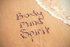Texto del alcohol de la mente del cuerpo escrito en la arena con resaca Fotografía de archivo