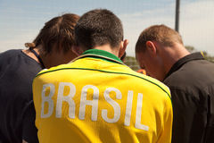 Texto del Brasil en la parte de atrás de la camisa de deporte amarilla - atletas jovenes que hablan la opinión trasera foto de archivo