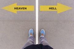 Texto del cielo o del infierno en la tierra, los pies y los zapatos del asfalto en piso fotografía de archivo libre de regalías