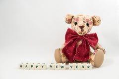 Texto del cubo de la Feliz Año Nuevo y oso de peluche blancos Fotos de archivo libres de regalías