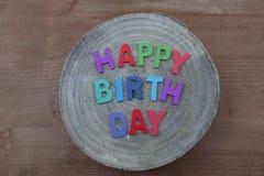 Texto del feliz cumpleaños con las letras de madera coloreadas en un tablero redondo de madera del mango imágenes de archivo libres de regalías