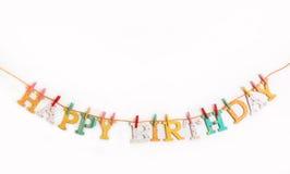 Texto del feliz cumpleaños con las letras de madera en un fondo blanco Foto de archivo libre de regalías