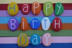 Texto del feliz cumpleaños con las piedras coloreadas sobre un tablero de madera coloreado multi foto de archivo libre de regalías