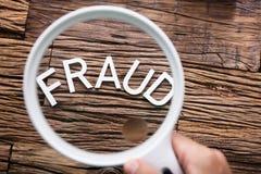 Texto del fraude a través de la lupa Fotos de archivo