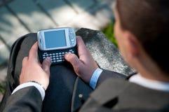 Texto del hombre de negocios por el teléfono móvil. Estudiante Fotos de archivo