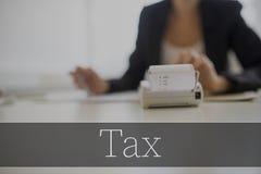 Texto del impuesto sobre la máquina sumadora con la empresaria Fotos de archivo libres de regalías